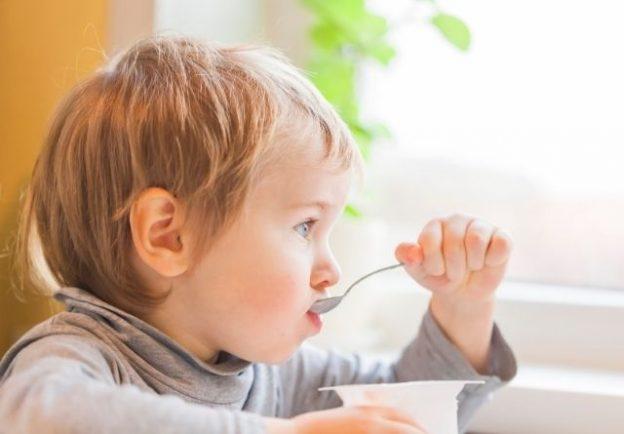 Un niño bebe un vaso de leche. Los lácteos son esenciales en la alimentación infantil